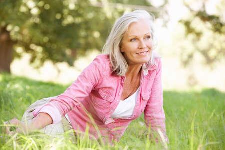 woman in field: Senior Woman Relaxing In Sunny Summer Field