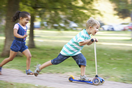 riding: Young Boy On Scooter In Park With Sister