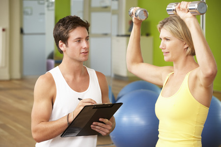 personal trainer: Woman Exercising Being Encouraged By Personal Trainer In Gym Stock Photo