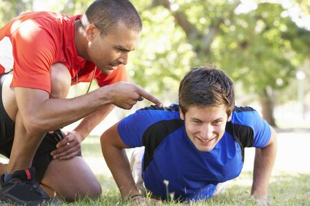 motivating: Young Man Working With Personal Trainer In Park