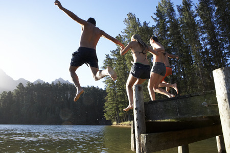 Group Of Young People Jumping From Jetty Into Lake