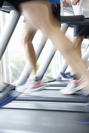 keeping fit: Close Up Of 3 Runners Feet On Running Machine In Gym Stock Photo