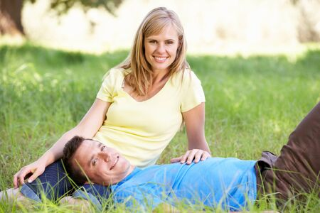 countryside loving: Couple Relaxing In Sunny Summer Field Stock Photo