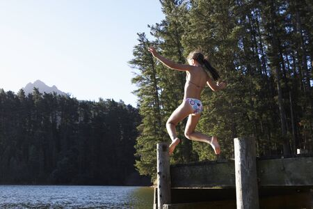 jetty: Girl Jumping From Jetty Into Lake Stock Photo