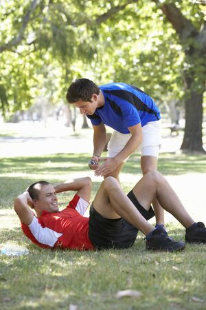 personal trainer: Young Man Working With Personal Trainer In Park