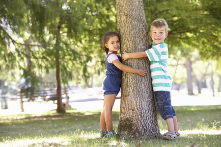 and four of the year: Two Children Hugging Tree In Park