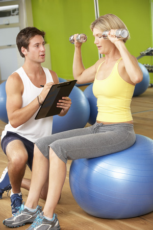 personal trainer woman: Woman Exercising Being Encouraged By Personal Trainer In Gym Stock Photo