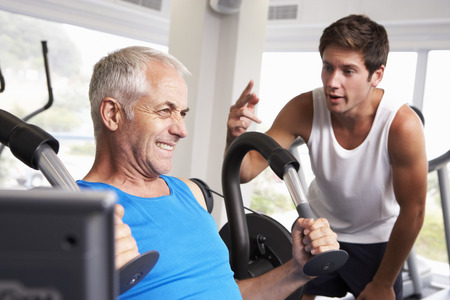 personal trainer: Middle Aged Man Being Encouraged By Personal Trainer In Gym