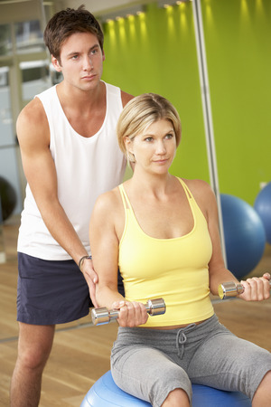 encouraged: Woman Exercising Being Encouraged By Personal Trainer In Gym Stock Photo