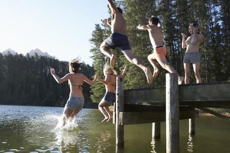 niño saltando: Grupo de jóvenes saltando de Embarcadero En El Lago Foto de archivo