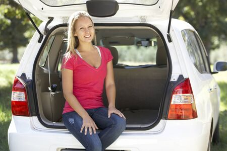 car trunk: Young Woman Sitting In Trunk Of Car Stock Photo