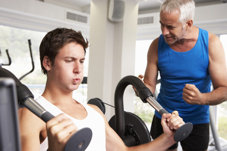 encouraged: Middle Aged Man Being Encouraged By Personal Trainer In Gym