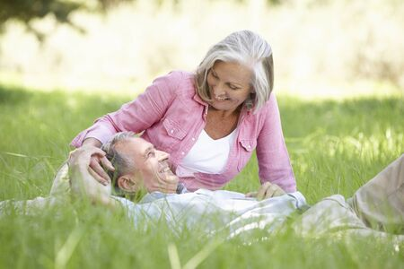 countryside loving: Senior Couple Relaxing In Sunny Summer Field Stock Photo