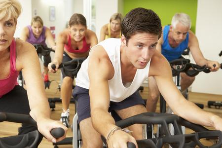 middle class: Grupo participa en clase de giro en gimnasia Foto de archivo