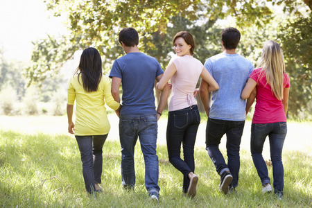countryside loving: Group Of Young Friends Walking Through Countryside Stock Photo