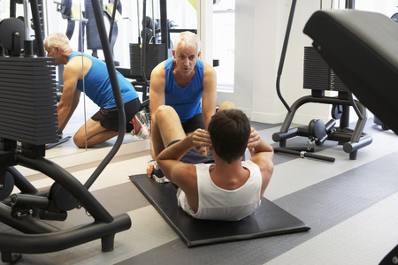 sit ups: Man Working With Personal Trainer In Gym Stock Photo