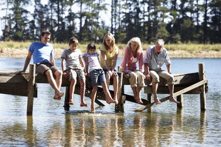 3 世代家族はアウト オーバー湖を探している木製の桟橋に座って