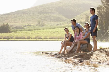 couple relaxing: Group Of Young People Relaxing At Shore Of Lake Stock Photo