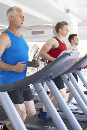 treadmill: Group Of Men Using Running Machines In Gym