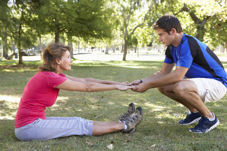 personal trainer woman: Senior Woman Working With Personal Trainer In Park
