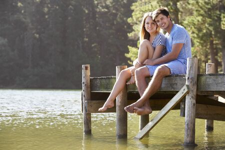 jetty: Young Romantic Couple Sitting On Wooden Jetty Looking Out Over Lake