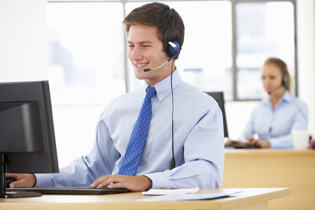 man working computer: Friendly Service Agent Talking To Customer In Call Centre Stock Photo