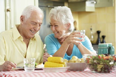 jubilados: Pareja mayor que come comida junto en cocina