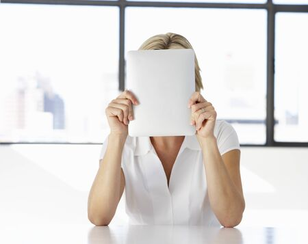digital tablet: Businesswoman Sitting At Desk In Office With Face Hidden Behind Digital Tablet Stock Photo
