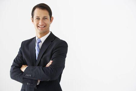 standing businessman: Studio Portrait Of Businessman Standing Against White Background Stock Photo