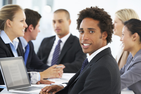 mixed age range: Portrait Of Male Executive With Office Meeting In Background Stock Photo