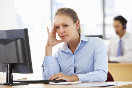 empleado de oficina: Empresaria tensionada Trabaja En El Escritorio En Oficina Ocupado Foto de archivo