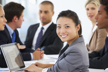 group of business people: Portrait Of Female Executive With Office Meeting In Background