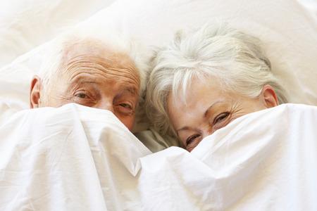 couple au lit: Senior Couple de détente au lit cachant sous Feuilles Banque d'images