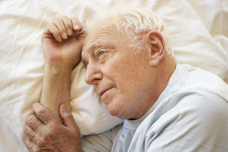 restless: Senior Man Relaxing In Bed Stock Photo
