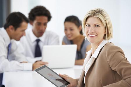 배경에서 Office 모임 태블릿 컴퓨터를 사용 하여 여성 집행의 초상화 스톡 콘텐츠