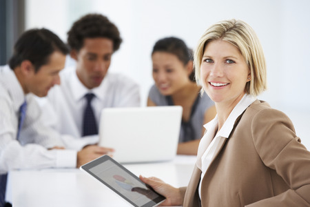 female executive: Portrait Of Female Executive Using Tablet Computer With Office Meeting In Background