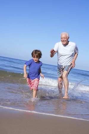 grandkid: Grandfather Chasing Grandson Along Beach Stock Photo