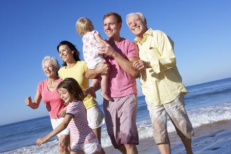 멀티 세대 가족이 함께 해변을 따라 실행