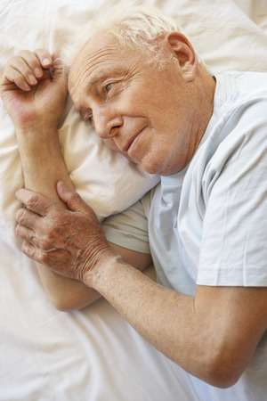 80s adult: Senior Man Relaxing In Bed Stock Photo