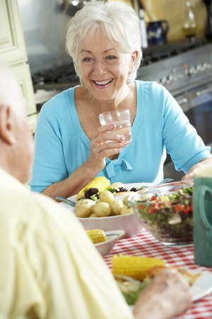 eating dinner: Senior Couple Eating Meal Together In Kitchen