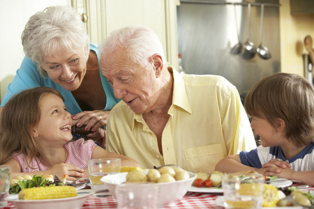 Grootouders en Kleinkinderen die maaltijd samen in keuken Stockfoto
