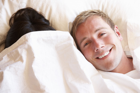 bedclothes: Couple Relaxing In Bed Hiding Under Bedclothes Stock Photo
