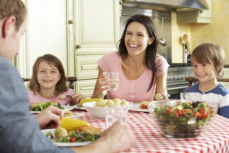 personas saludables: Familia que come la comida junto en cocina