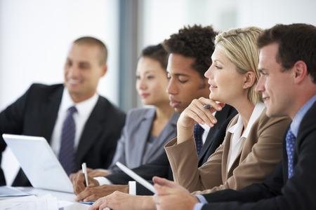 Een groep mensen uit het bedrijfsleven luisteren naar collega Addressing Office Meeting Stockfoto - 42251507