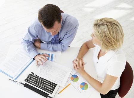 personas hablando: Vista desde arriba de la empresaria y empresario en informaciones de trabajo conjunto