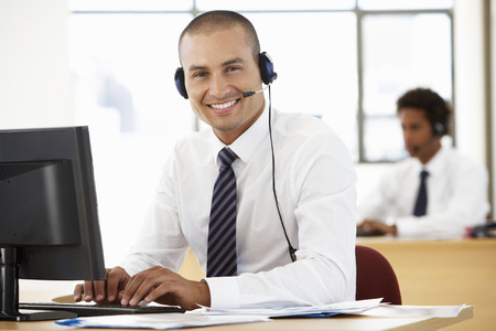 telephone headsets: Friendly Service Agent Talking To Customer In Call Centre Stock Photo