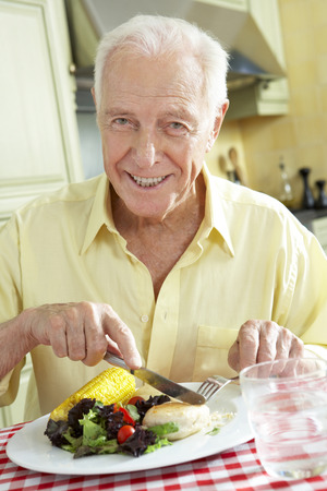 Senior Man Eating Meal In Kitchen