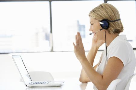 office women: Businesswoman Sitting At Desk In Office Using Laptop Wearing Headset Stock Photo