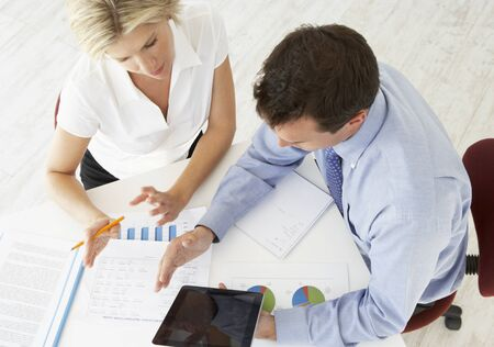 Overhead View Of Businesswoman And Businessman Working At Desk Together