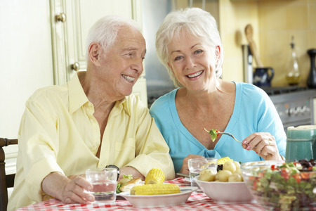 senior eating: Senior Couple Eating Meal Together In Kitchen